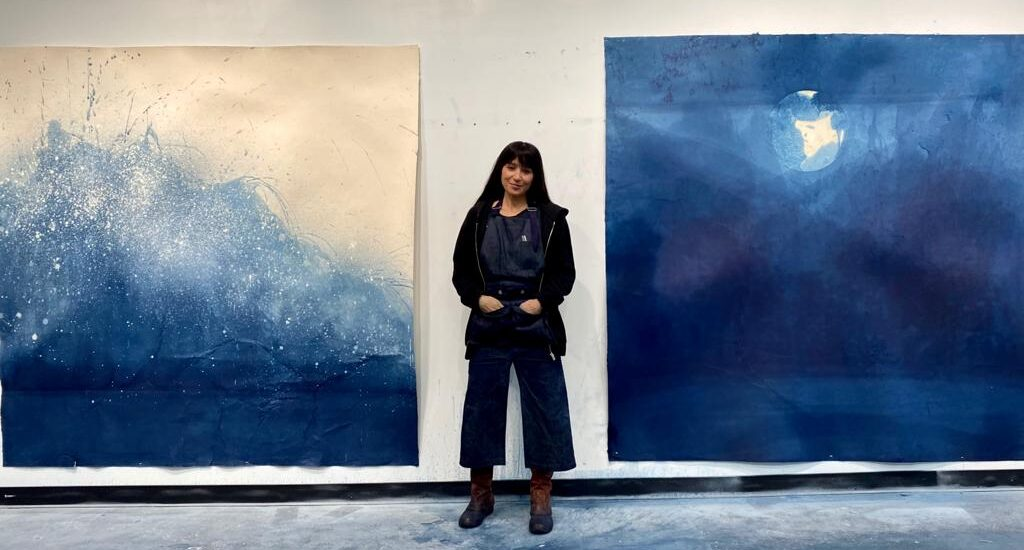 Miya standing with her latest indigo-infused works on handmade paper Photo courtesy of :Gregory de la Haba