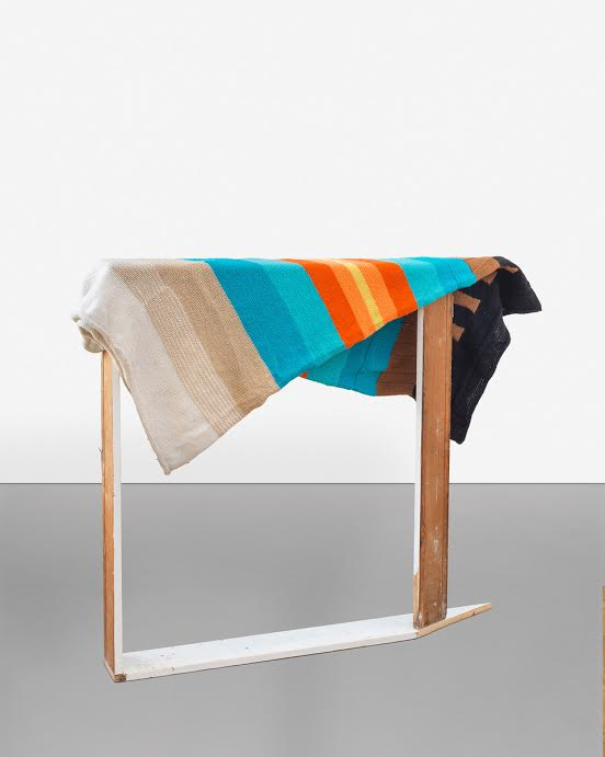 Tomashi Jackson Bench with a rainbow quilt on it